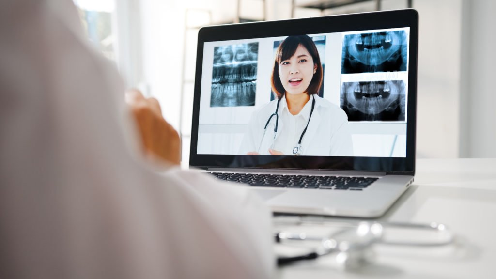 Woman speaking on laptop in front of dental x-rays. 6Connex case study or FMC's virtual event.